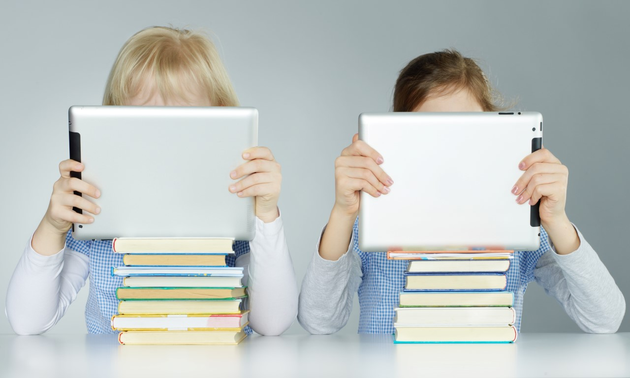 children reading iPads on top of books